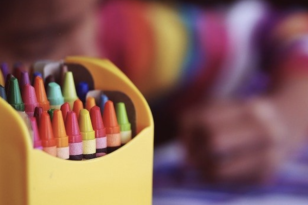 blurry photo of child coloring with crayons
