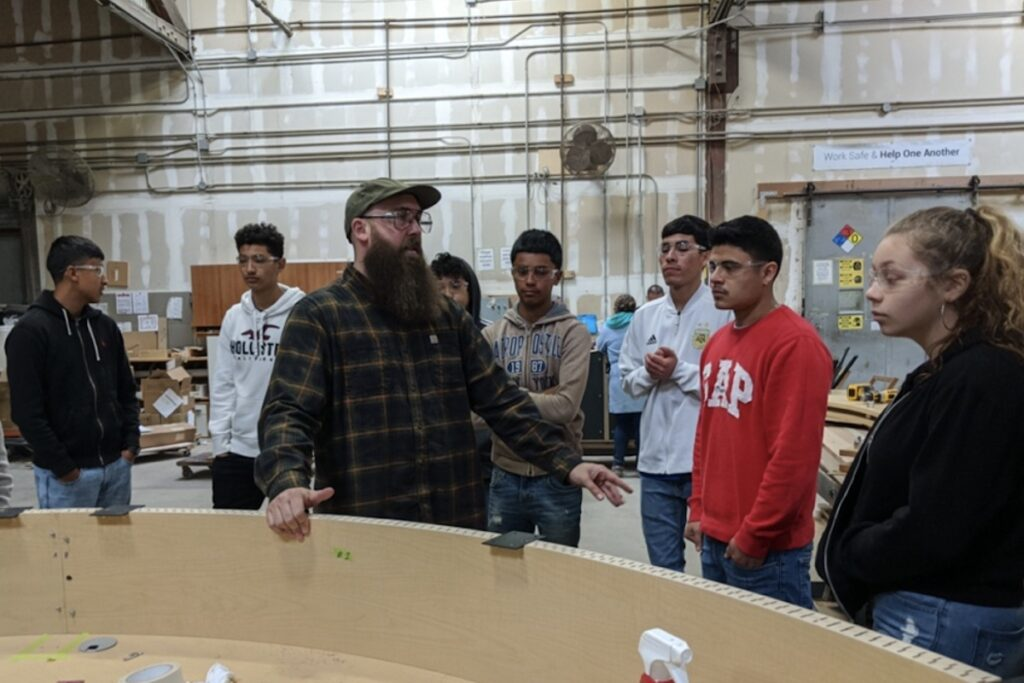 High school students listen as a worker at Creative Wood explains how to make a rounded reception desk during a Manufacturing Day factory tour in 2019.